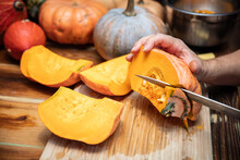 Man Is Cutting A Fresh Pumpkin, Various Sort In The Background, Preparation In The Kitchen