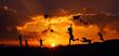 Sylwetki dzieci puszczających latawce o zachodzie słońca