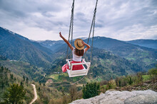 Free Romantic Woman Traveler With Open Arms Enjoying Of Swinging On Heavenly Swing And Mountain View. Calm And Quiet Wanderlust Concept Moment When Person Feels Happiness Life And Freedom
