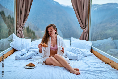 Fototapeta Cute happy gorgeous sleepy waking up woman with slim long legs wearing bathrobe sitting on white bed at hotel room with big windows during morning breakfast. Beginning start new day obraz