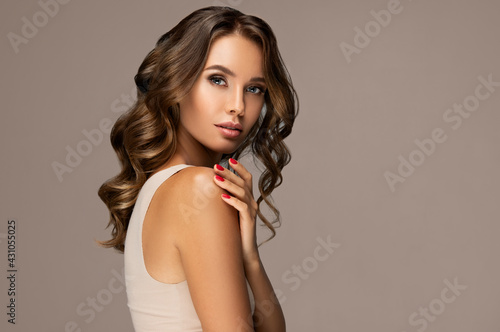 Beautiful woman in profile with long and shiny wavy hair . Beauty model girl with curly hairstyle . Fashion, cosmetics and makeup