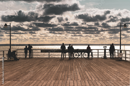 People on pier during sunset - fototapety na wymiar