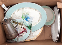 Discarded Fine China, Liqueur Stemware, And An Old Espresso Coffee Maker In A Plain Brown Box