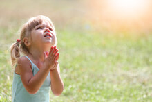 Little Girl Praying In Nature