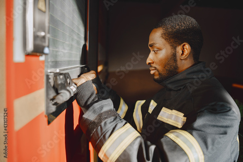 Fotografia, Obraz Portrait of a firefighter standing in front of a fire engine