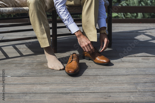 Fotografie, Obraz Male is lacing elegant brown shoes sitting on the bench outside