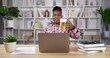 Happy african man drink beer and video call on laptop