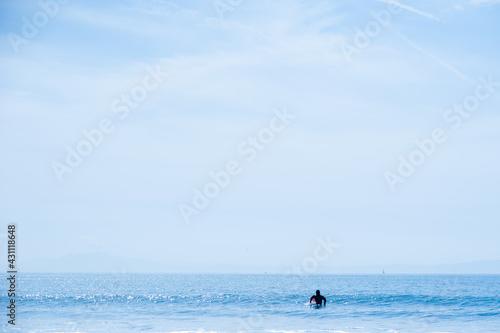 Fotografia 水平線が見える海原で波を待つサーファー