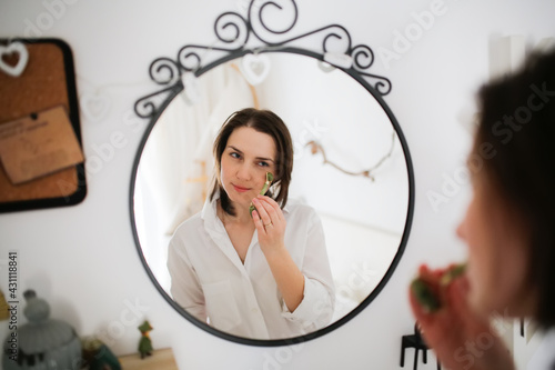 Photographie Cute caucasian woman with Jade Massage Roller near mirror ,female brunette does facial massage with roller, gouache