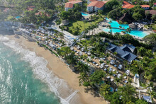 Aerial Shot Of Beach Surrounded By A Resort Area And Sea Under The Sunlight