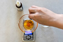 A Soap-maker Woman Weighs Aromatic Oils For Making Cosmetics On A Kitchen Scale. Home Spa. Small Business
