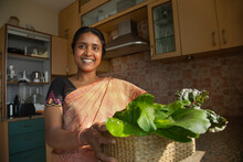 A Smiling Woman With Home-grown Green Leafy Vegetables