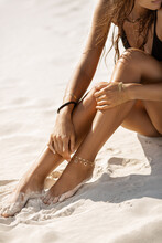 Woman Sitting On The Beach With Bracelets