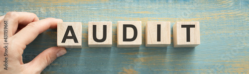 Fotografia The word AUDIT is written on wooden cubes on a wooden table near a pen and magnifier
