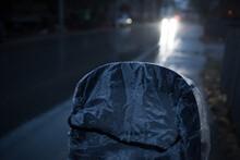 Kinderwagenverdeck Mit Regenschutz Bei Regen In Dunkelheit, Beleuchtung Von Entgegenkommenden Autos Spiegelt Sich Im Nassen Asphalt