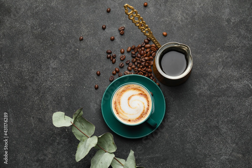 Fototapeta Cup of hot cappuccino and coffee pot on dark background obraz