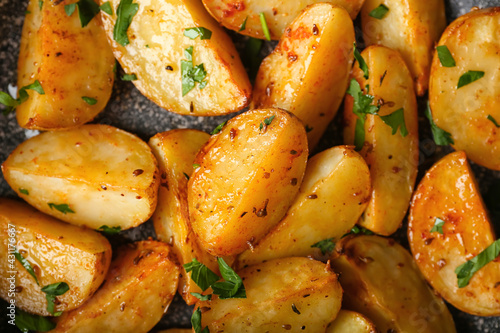Tasty fried potatoes with parsley, closeup