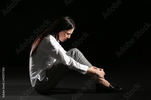 Fotografía Sad young woman sitting on dark background