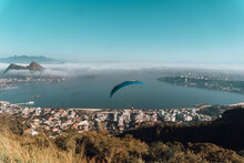 Paraglider Gliding Over Tall Grass And Trees In Niteroi City Park