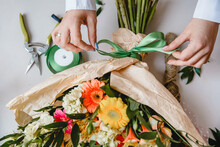 A Female Florist Ties A Green Ribbon Bow On A Bouquet Of Flowers Wrapped In Craft Paper On The Desktop. Top View.