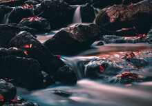 Closeup Of A River With Long Exposure Surrounded By Rocks Under The Sunlight