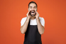 Young Expressive Man Barista Bartender Barman Employee In Black Apron White T-shirt Work In Coffee Shop Scream News With Hands Near Mouth Isolated On Orange Background Studio Small Business Startup.