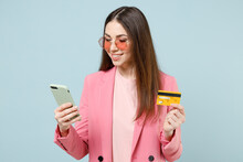Young Fun Smiling Happy Caucasian Woman 20s Wear Pastel Pink Clothes Glasses Using Mobile Cell Phone Credit Bank Card Isolated On Blue Background Studio Portrait. People Lifestyle Technology Concept.