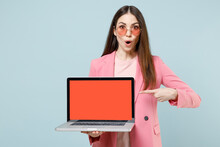 Young Shocked Confused Woman In Pastel Pink Clothes Glasses Point Index Finger On Laptop Pc Computer Blank Screen Workspace Area Isolated On Blue Background Studio People Lifestyle Technology Concept