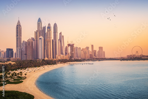 Fototapeta Sunset view of the Dubai Marina and JBR area and the famous Ferris Wheel and golden sand beaches in the Persian Gulf