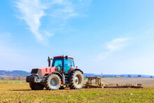 A Farmer Plows The Soil In The Field With A Chisel Plow On A Tractor. Agricultural Tractor With A Plow On Farmland.