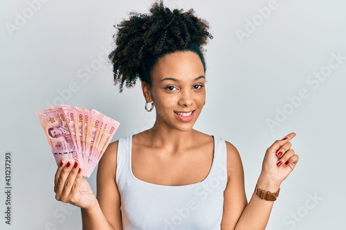 Fotografia, Obraz Young african american girl holding thai baht banknotes smiling happy pointing w