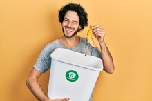 Handsome Hispanic Man Recycling Banana Peel Composting Organic Fertilizer Winking Looking At The Camera With Sexy Expression, Cheerful And Happy Face.