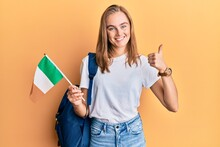Beautiful Blonde Woman Exchange Student Holding Ireland Flag Smiling Happy And Positive, Thumb Up Doing Excellent And Approval Sign