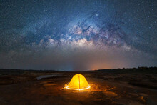 Camping Tent Under Sky On Mountain Hills With The Milky Way With Bright Stars At Night In Travel On Holiday Vacation Concept. Natural Universe Space Landscape Background. Adventure Tourist Activity.