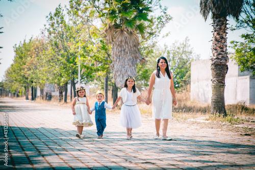 Fotografie, Obraz Mamá mexicana paseando feliz con sus hijos en un parque