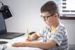 Little boy in glasses does homework sitting at the desk.