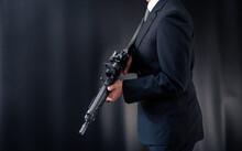 アサルトライフルを構えるスーツ姿の人物