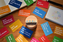 There Is A Table With A Card With The SDG Goals And A Ball Of Earth, A Small Sketchbook With SDG Symbols And A Wooden Cube Stamped With The Letters SDGs.