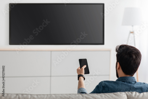 Young man watching television and using smart TV remote control application on smartphone, back view