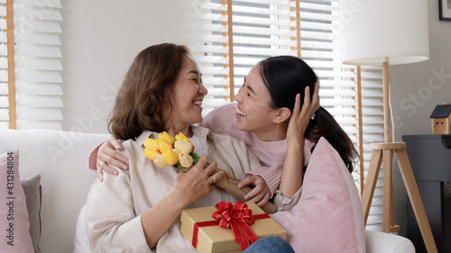 Fototapeta Attractive beautiful asian middle age mum sit with grown up daughter give gift box and flower in family moment celebrate mother day. Overjoy bonding cheerful kid embrace relationship with retired mom. obraz