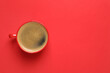 Leinwandbild Motiv Cup of aromatic coffee on red background, top view. Space for text