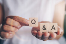Q And A Alphabet On Wooden Cube In Hand Hold With Background. Question And Answer Meaning.