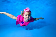 Charming Little Girl Dives And Swims In The Pool Near The Bottom In A Beautiful Pink Dress And A Bow On Her Head. She Has Her Arms Outstretched And Is Looking At The Camera. Portrait. Horizontal View.