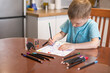 The child boy does tasks for the development of logical thinking, classes with a speech therapist at home, neuropsychology, autism, homework.