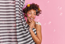 Cheerful Dark Skinned Woman Takes Shower In Bathroom Washes Herself Applies Foaming Gel On Body Hides Behind Curtain Looks Away Isolated Over Pink Background With Soap Bubbles. Home Spa Effect