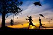 Sylwetki dzieci bawiące się latawcami i na huśtawce