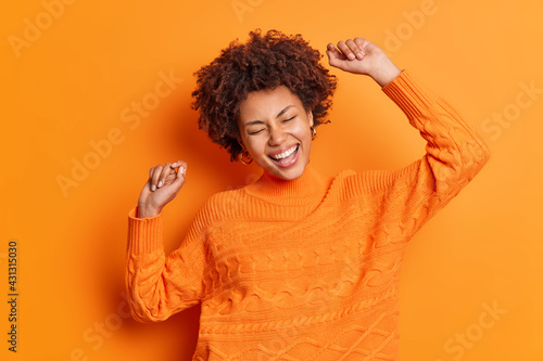 Fotografie, Obraz Ecstatic carefree woman with Afro hair dances with arms raised up smiles broadly makes winner gesture celebrates triumph wears orange jumper poses indoor