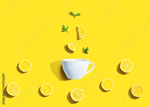 Fresh yellow lemons with tea cup overhead view