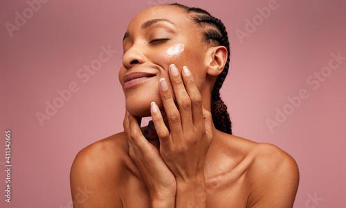Fototapeta Woman using moisturizer on her face obraz