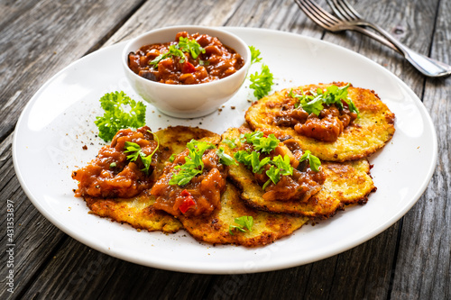 Potato pancakes with vegetable stew on wooden table